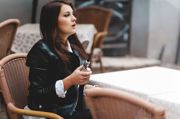 Moça bonita, segurando o cigarro eletrônico na mão enquanto está sentado em uma mesa de café