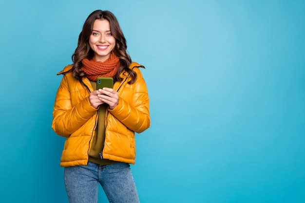 Moça bonita segurando um telefone com um sorriso dentuço usar blusão de outono