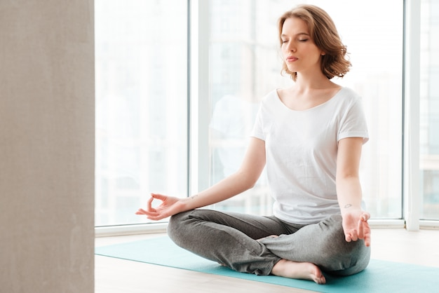 Moça bonita sentada perto da janela, fazer exercícios de ioga.