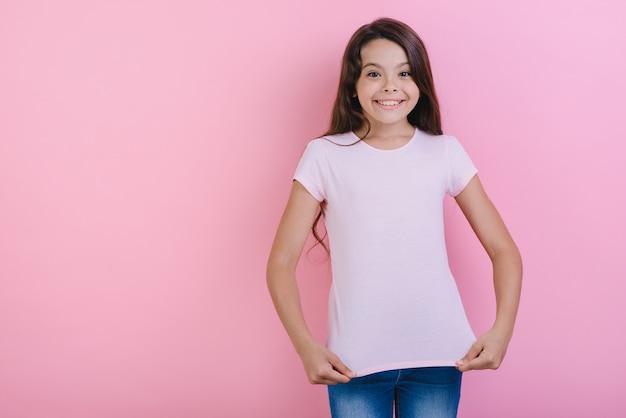 Moça bonita sobre studiotouches cor-de-rosa seu t-shirt que olha a câmera.