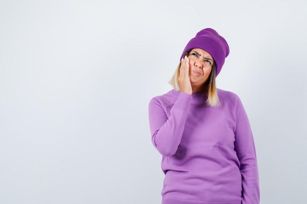 Moça bonita, sofrendo de dor de dente, olhando para cima com suéter, gorro e parecendo desconfortável, vista frontal.