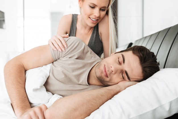 Moça bonita sorridente, acordando o marido dormindo na cama