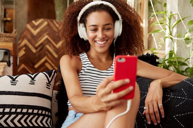 Moça bonita tem penteado afro, faz videochamada pelo smartphone e fones de ouvido, fala com um amigo online enquanto se senta no confortável sofá com almofadas.