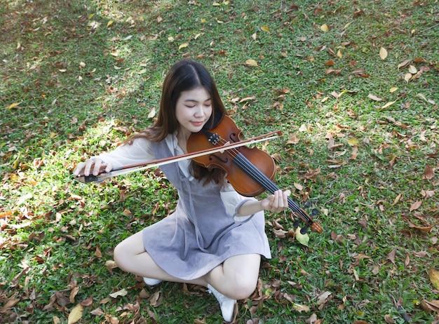 Moça bonita tocando violino em um parque. é hora de relaxar, com sentimento de felicidade, o reflexo da luz do sol está brilhando em torno da grama verde do piso térreo