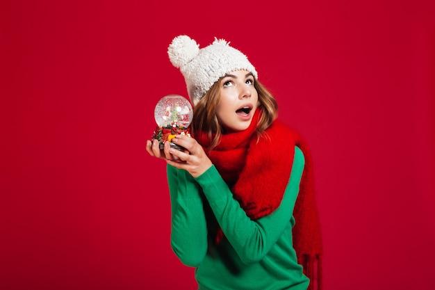 Moça bonita usando chapéu e cachecol quente segurando o brinquedo de natal
