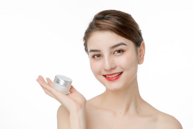 Moça bonita usando creme hidratante para cuidados com a pele do rosto
