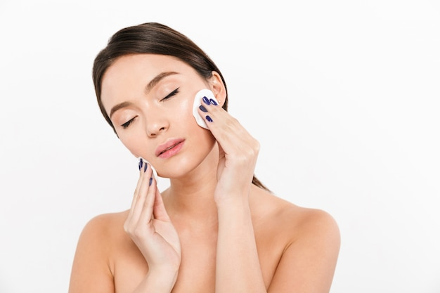 Moça bonita usando esponjas para remover maquiagem isolado