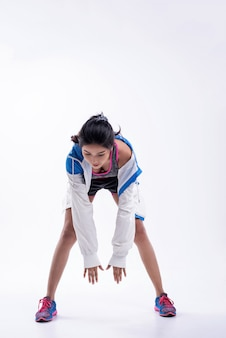 Moça bonita vestindo sportwear e jaqueta, tentando alcançar as mãos no chão
