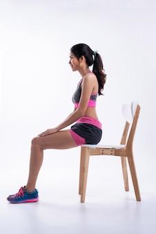Moça bonita vestindo sportwear. sentado na cadeira de madeira