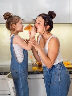 Moça bonito que compartilha do croissant com a mãe
