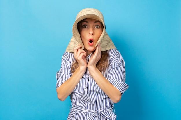 Moça chocada em um chapéu e vestido em uma parede azul. conceito de férias, verão e viagens