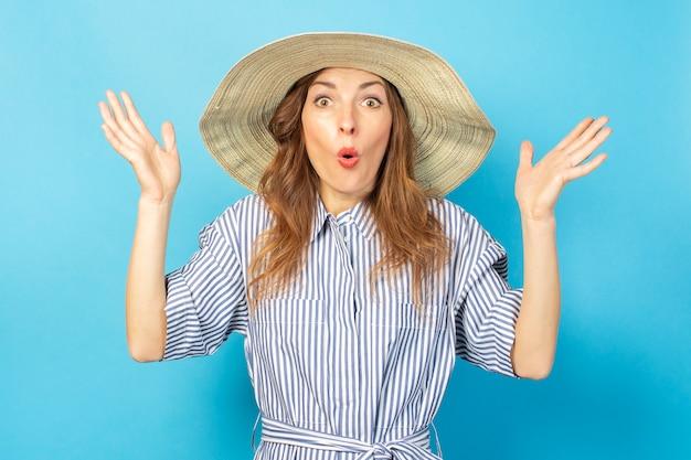 Moça chocada em um vestido e chapéu em uma parede azul. conceito de férias, verão e viagens