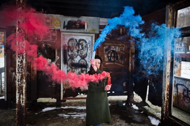 Moça com a bomba de fumaça colorida azul e vermelha nas mãos.