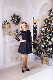 Moça com árvore de natal e lareira