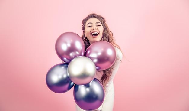 Moça com balões em uma parede colorida