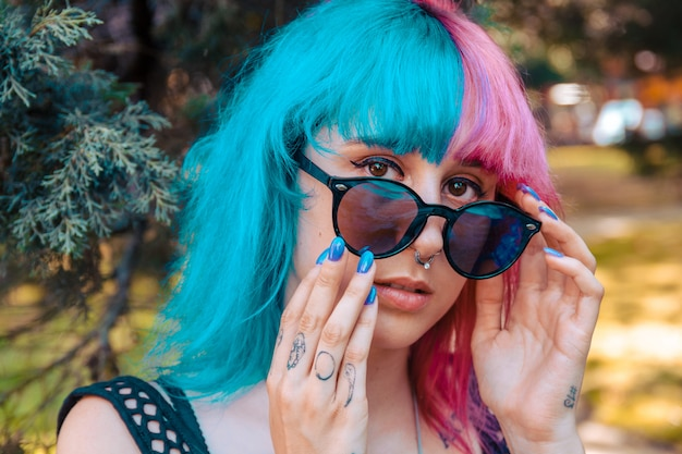 Moça com cabelos coloridos em azul e rosa, segurando um par de óculos de sol