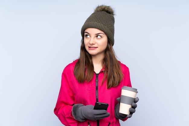 Moça com chapéu do inverno na parede azul que guarda o café para levar embora e um móvel ao pensar em algo