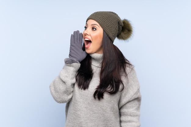 Moça com chapéu do inverno sobre a parede azul que grita com a boca aberta