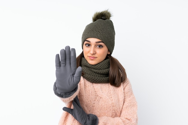 Moça com chapéu do inverno sobre o branco isolado que faz o gesto de parada com a mão