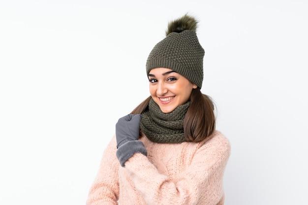 Moça com chapéu do inverno sobre o fundo branco isolado, comemorando uma vitória