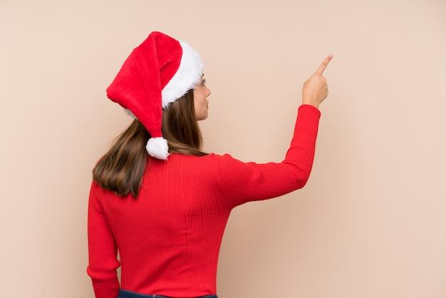 Moça com chapéu do natal sobre a parede isolada que aponta para trás com o dedo indicador
