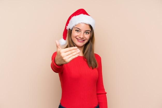 Moça com chapéu do natal sobre a parede isolada que convida a vir