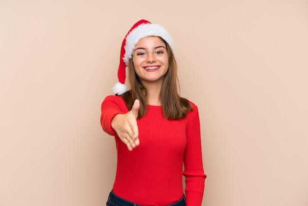 Moça com chapéu do natal sobre o aperto de mão isolado da parede após o bom negócio