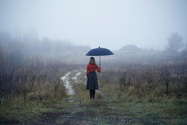 Moça com guarda-chuva no campo do outono
