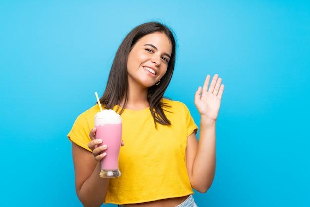 Moça com milk-shake de morango sobre parede isolada, saudando com mão com expressão feliz