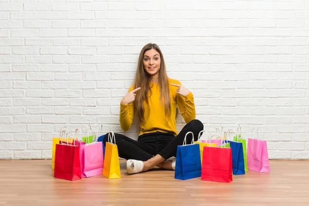 Moça com muitos sacos de compras com expressão facial de surpresa