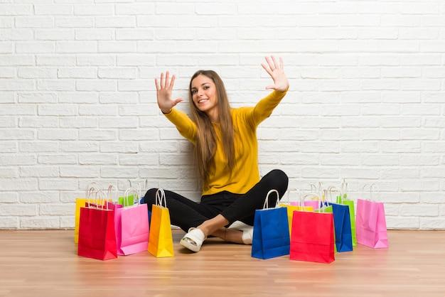 Moça com muitos sacos de compras, contando dez com os dedos