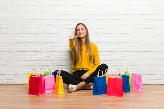 Moça com muitos sacos de compras, dando um gesto do polegar para cima, porque algo de bom aconteceu