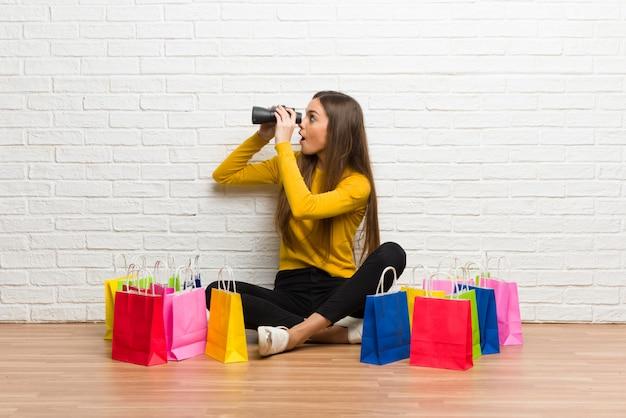 Moça com muitos sacos de compras e olhando à distância com binóculos