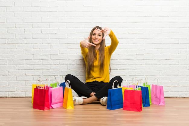 Moça com muitos sacos de compras, focando o rosto.