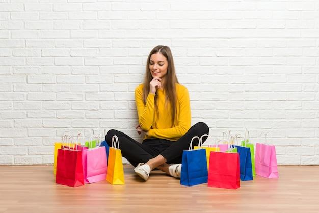 Moça com muitos sacos de compras, olhando para baixo com a mão no queixo