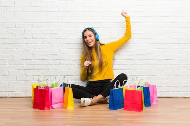 Moça com muitos sacos de compras, ouvindo música com fones de ouvido e dançando