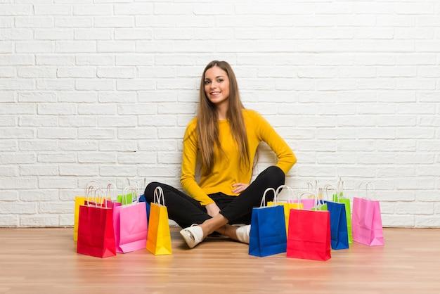 Moça com muitos sacos de compras posando com os braços no quadril e sorrindo