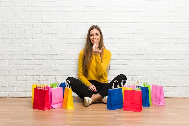Moça com muitos sacos de compras que convidam para vir com mão
