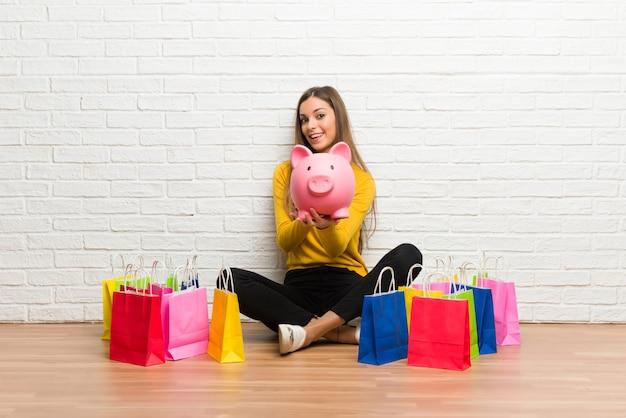 Moça com muitos sacos de compras que guardam um piggybank