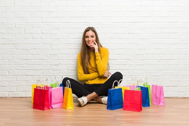 Moça com muitos sacos de compras que sorriem com uma expressão doce