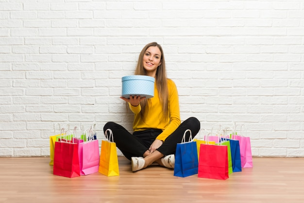 Moça com muitos sacos de compras, segurando um presente nas mãos