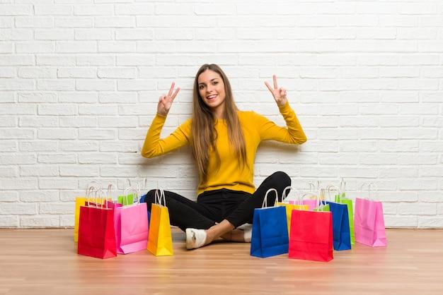 Moça com muitos sacos de compras, sorrindo e mostrando sinal de vitória com as duas mãos