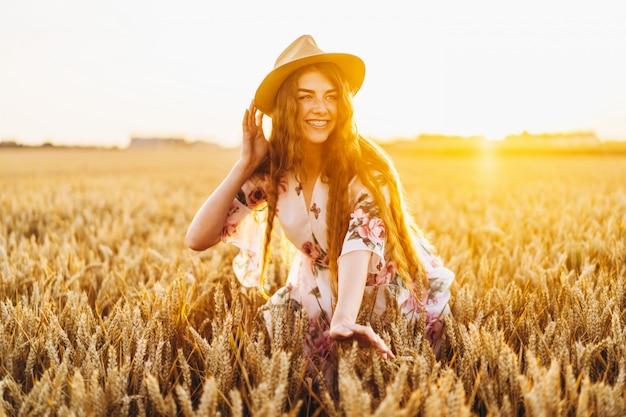 Moça com o cabelo encaracolado longo e as sardas enfrentam, no chapéu, no vestido branco claro com estampa floral, parado no campo de trigo, posando para a câmera, no pôr do sol do fundo.