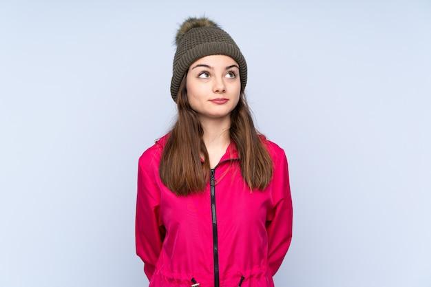 Moça com o chapéu do inverno isolado no azul e olhando para cima