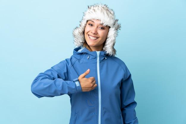 Moça com o chapéu do inverno isolado no azul que dá um polegar para cima gesto