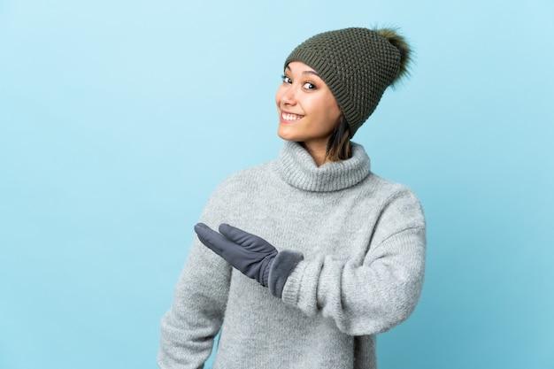Moça com o chapéu do inverno isolado no azul que estende as mãos ao lado para convidar a vir