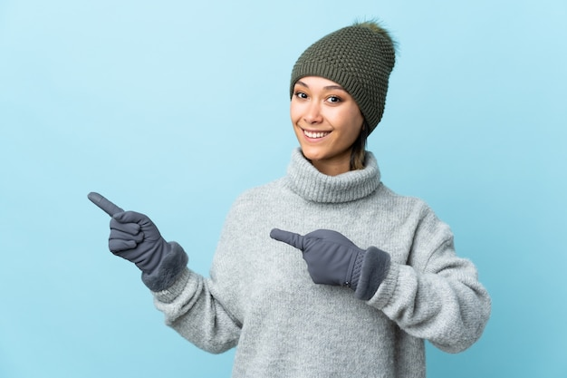 Moça com o chapéu do inverno isolado no dedo apontando azul para o lado