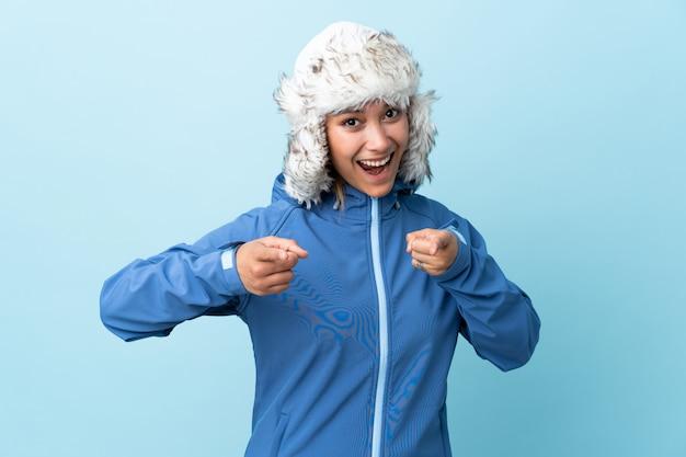 Moça com o chapéu do inverno isolado no dedo azul dos pontos em você