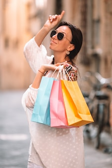 Moça com os sacos de compras na rua estreita em europa.