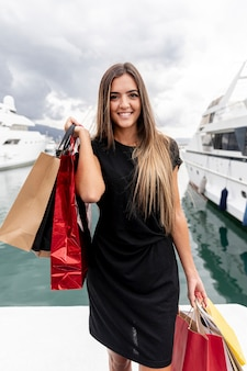 Moça com sacos de compras do outro lado do porto
